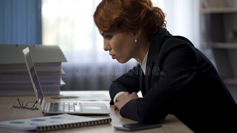 工作疲乏的女商人整夜艰苦看完成的报告,最后期限 图库摄影