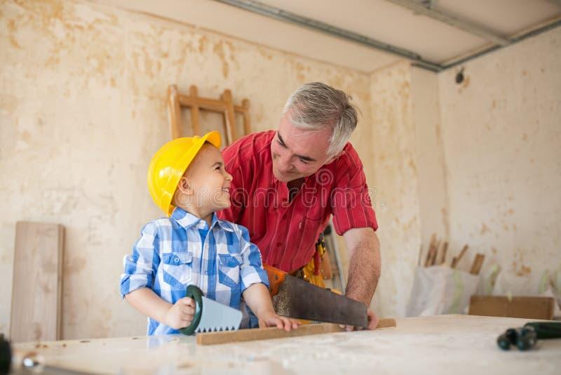 工作的乐趣祖父和孙子在木匠` s车间 库存照片
