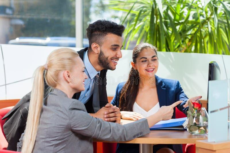 工作的商人看计算机,关于会议,小组买卖人微笑,队合作开会的讨论 免版税库存图片