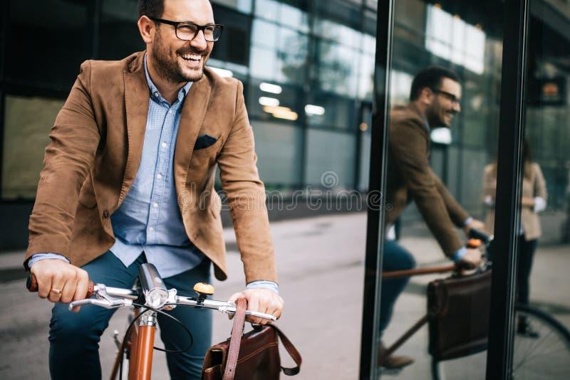 工作的愉快的商人骑马自行车在早晨 库存图片