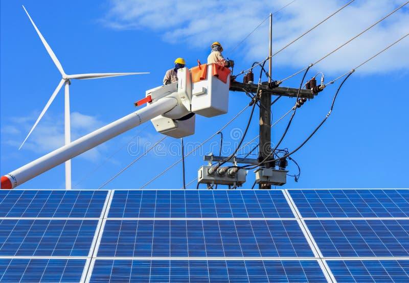 工作的电工修理输电线的导线与太阳电池板和风轮机的 库存照片