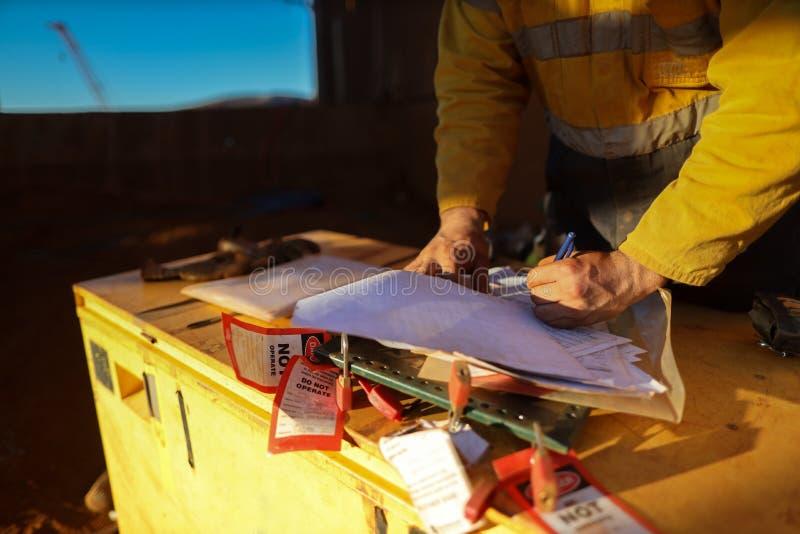工作的矿工标志在高度,在隔离锁箱子的有限空间许可证在完整绳索通入以后 免版税图库摄影