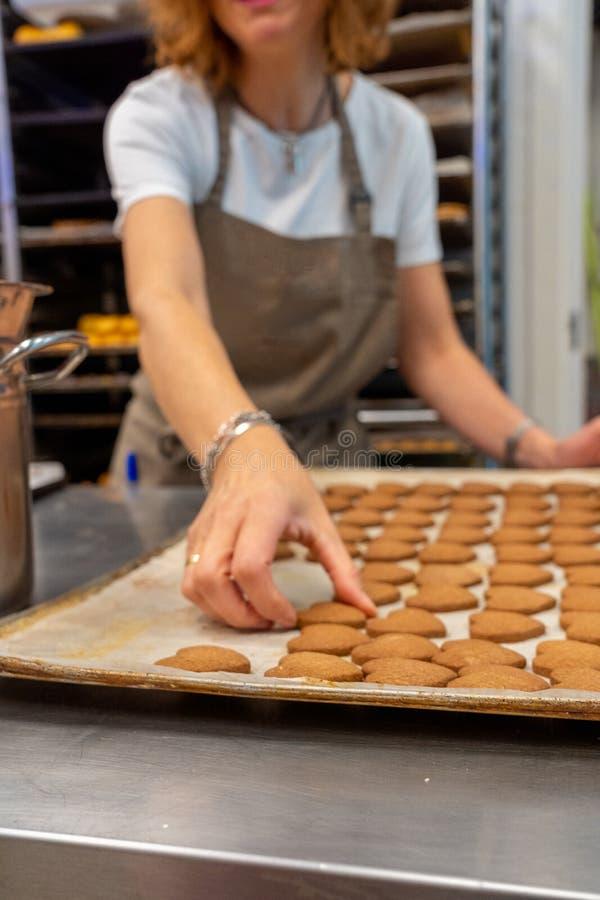 工作的糖果商,去掉茶面团,从烤箱盘子的曲奇饼 免版税库存照片