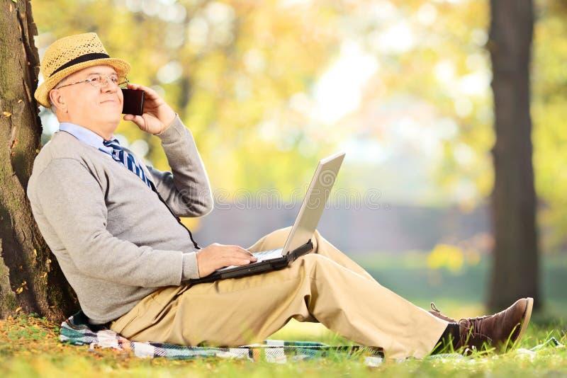 工作的老人坐在公园,谈话在电话和  免版税库存图片
