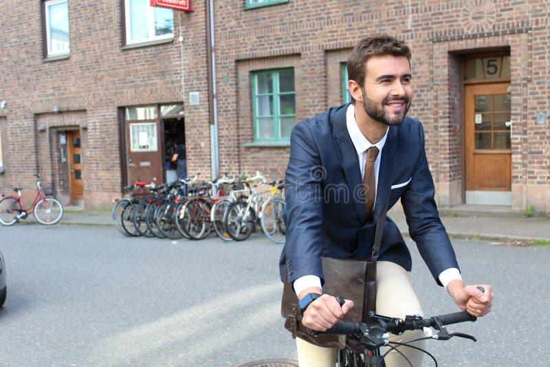工作的英俊的商人标题在自行车旁边 免版税库存照片