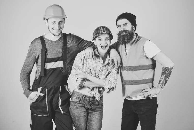 工作的队 修理旅团概念 配合,服务周到,旅团 男人和妇女有微笑的面孔的在盔甲和 免版税库存照片