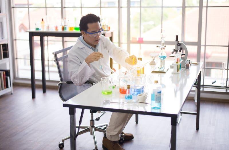 工作科学家亚裔的人投入医疗化学制品样品在试管在实验室 免版税库存照片