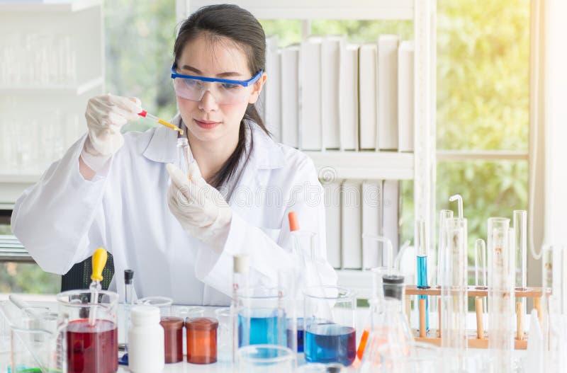 工作科学家的美女投入医疗化学制品样品在试管在实验室 免版税库存照片