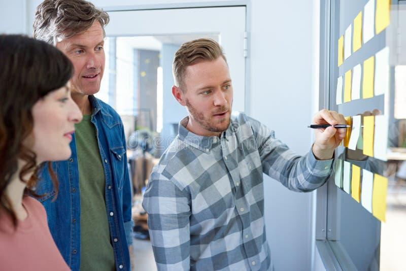 工作群策群力与稠粘的笔记的同事在办公室墙壁 免版税库存照片