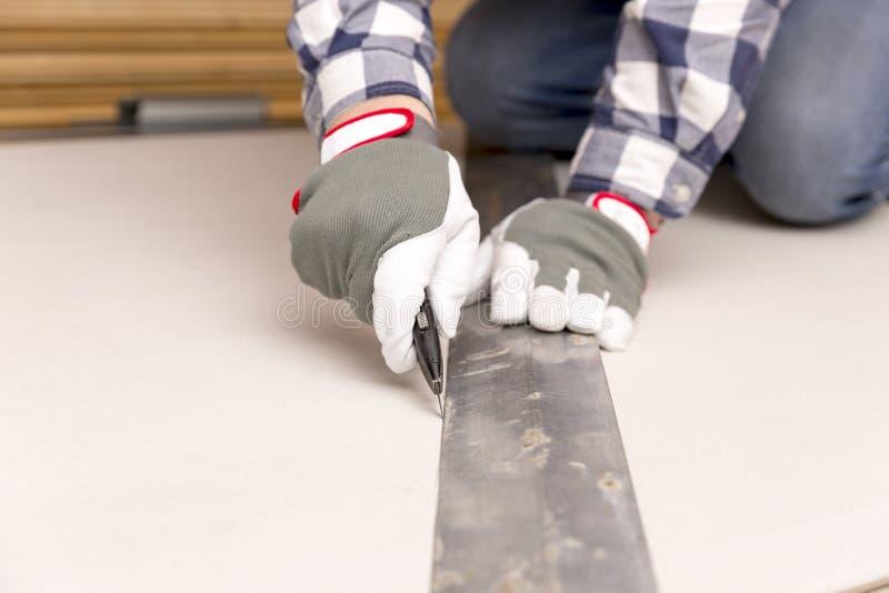 工作者与建筑刀子的切口石膏板 顶楼renov 库存图片