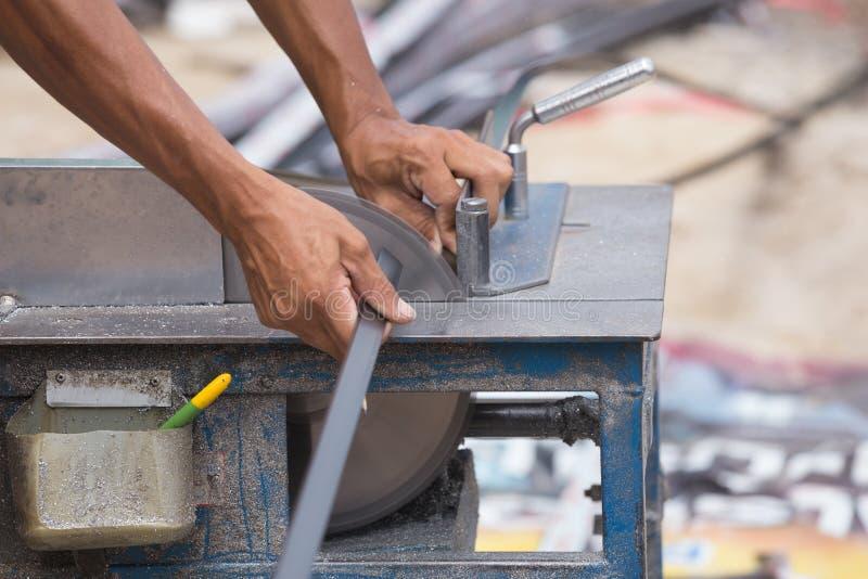 工作者与研磨机刀片的切口铝 图库摄影