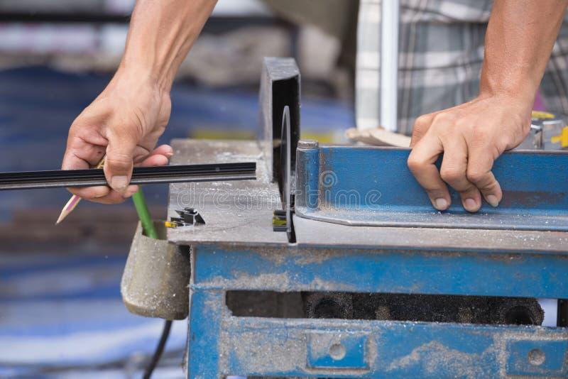 工作者与研磨机刀片的切口铝 免版税图库摄影