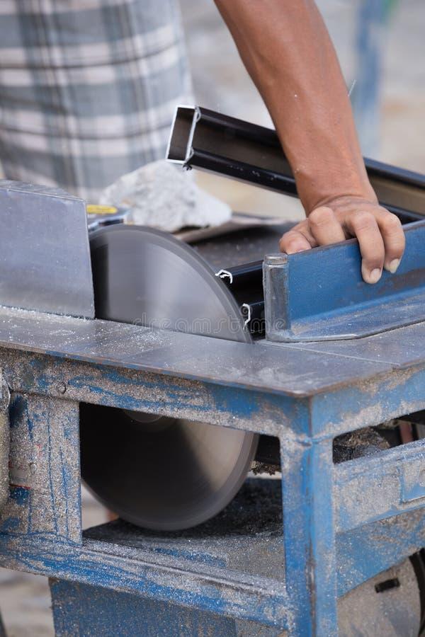 工作者与研磨机刀片的切口铝 免版税库存图片