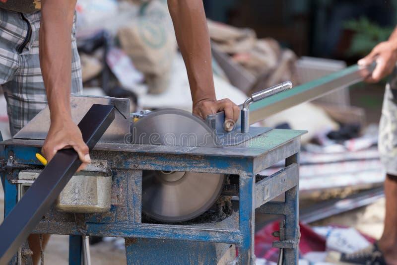 工作者与研磨机刀片的切口铝 免版税库存照片