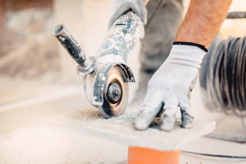 工作者与研磨机的切口石头 拂去灰尘,当研石路面时 免版税库存照片