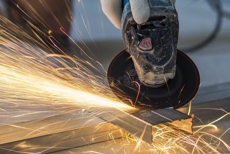 工作者与研磨机的切口金属特写镜头  发火花,当咧嘴时 免版税库存照片