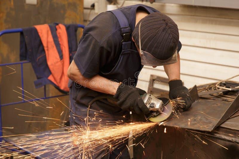 工作者与研磨机的切口金属特写镜头  研的铁火花 免版税图库摄影