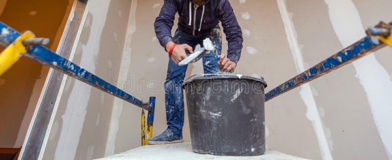 工作者与铺平的天花板调色板刀子一起使用从木平台在公寓里屋子是inder 免版税库存照片