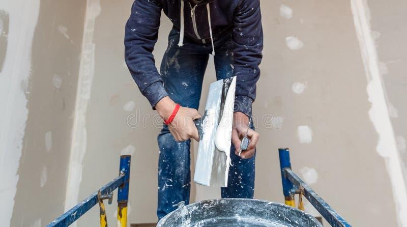 工作者与铺平的天花板调色板刀子一起使用从木平台在公寓里屋子是inder 库存图片