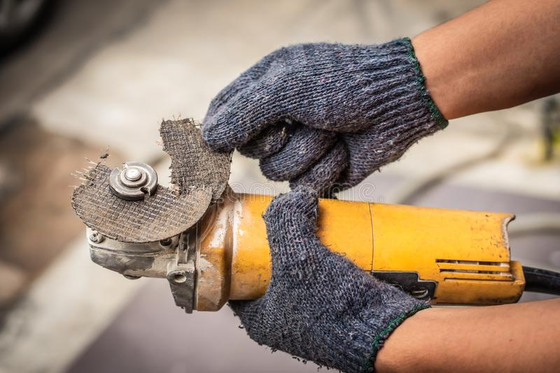 工作者人举行打破的研磨机刀片的手 使用的危险 库存图片
