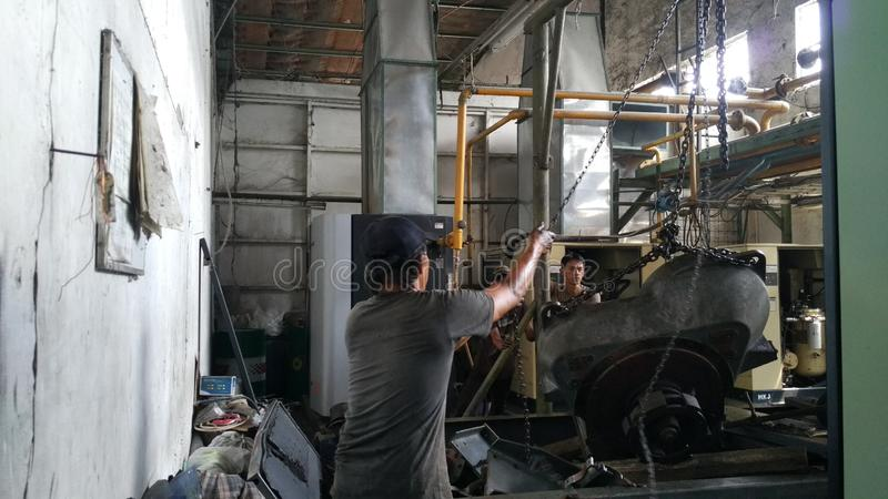 工作者体验严重损伤的修理工业机械 压缩机引擎修理  库存照片