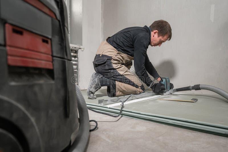 工作者使用一个修造的工具、碾碎的工具和吸尘器 在九十度的干式墙 库存照片