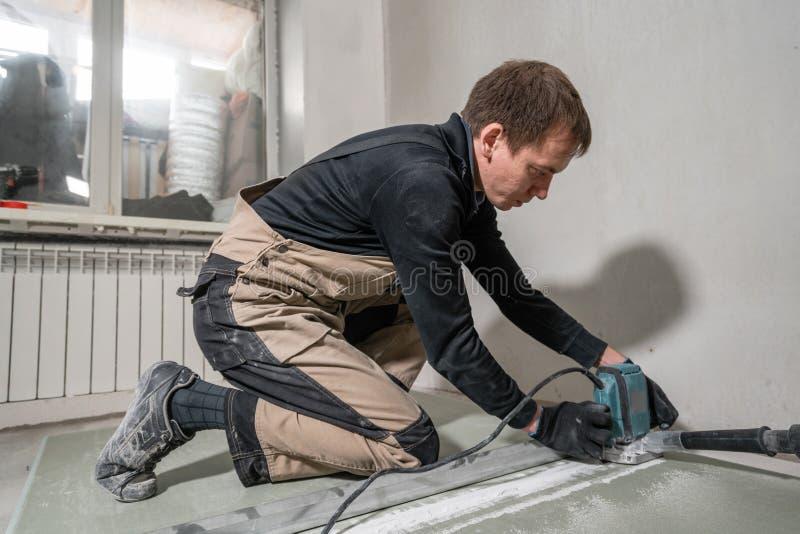 工作者使用一个修造的工具、碾碎的工具和吸尘器 在九十度的干式墙 免版税库存图片