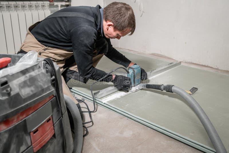 工作者使用一个修造的工具、碾碎的工具和吸尘器 在九十度的干式墙 库存图片