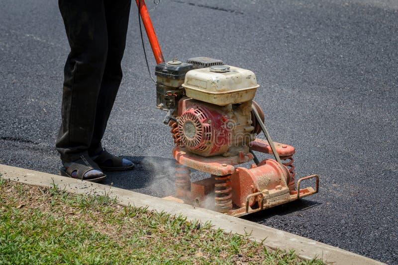工作者使用振动压路机变紧密的沥青在路修理 免版税库存照片