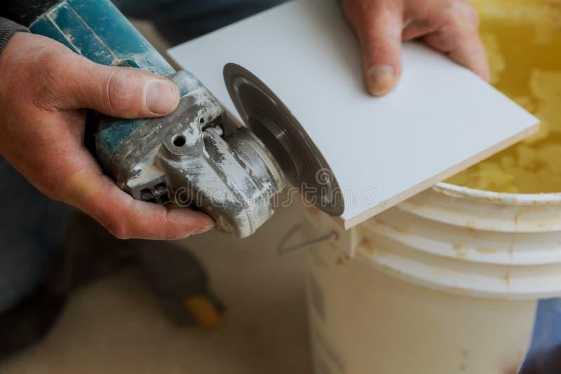 工作者使用研磨机裁减的切口瓦片成陶瓷地垫层数  免版税库存图片