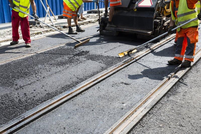工作者修建柏油路和铁路线 免版税库存图片