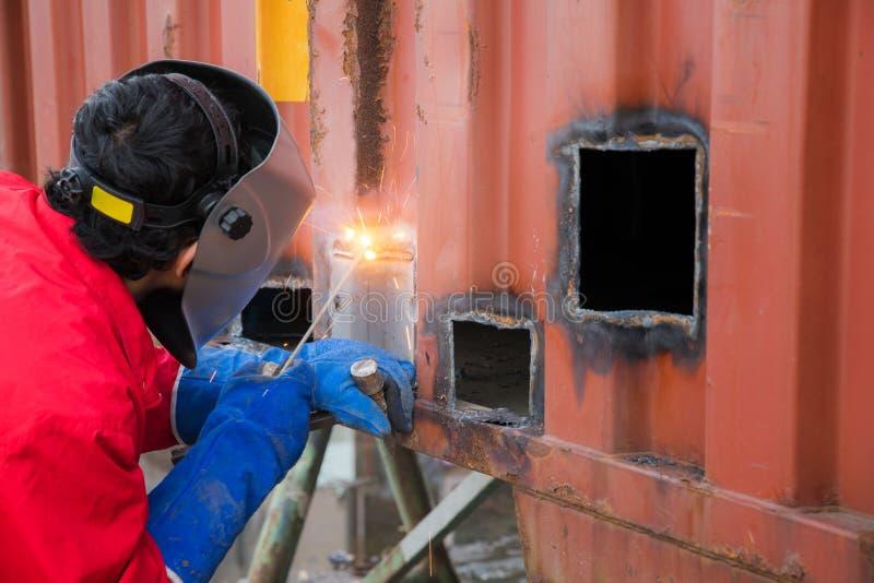 工作者修理由气割和焊接的容器箱子 免版税图库摄影