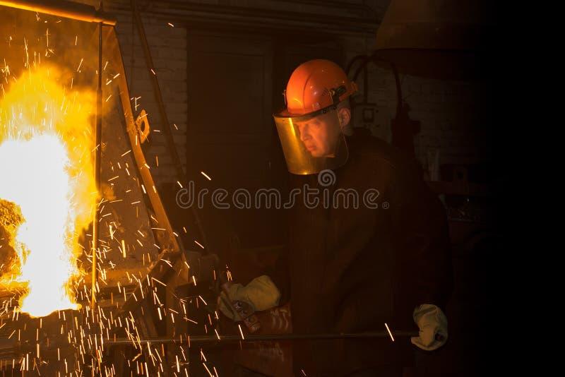 工作者倾吐从熔炉的熔化金属入杓子 免版税库存照片