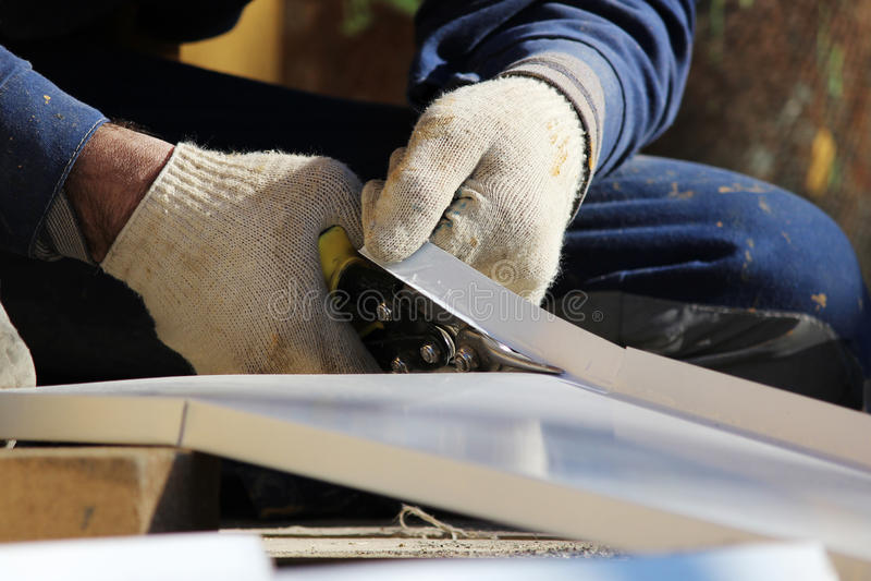 工作者做sladding在被恢复的大厦的窗口在城市,切开倾斜的金属板与剪刀 免版税库存照片