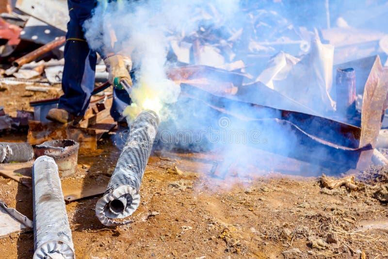 工作者切开与乙炔火炬的废金属 免版税库存照片