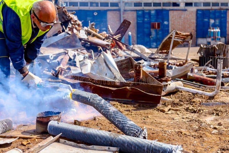 工作者切开与乙炔火炬的废金属 库存图片