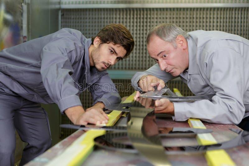 工作者切开与切削刀的金属板 免版税库存照片