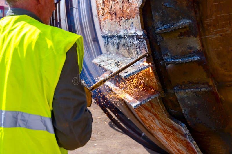 工作者切开老有乙炔火炬的金属工业设备 免版税图库摄影