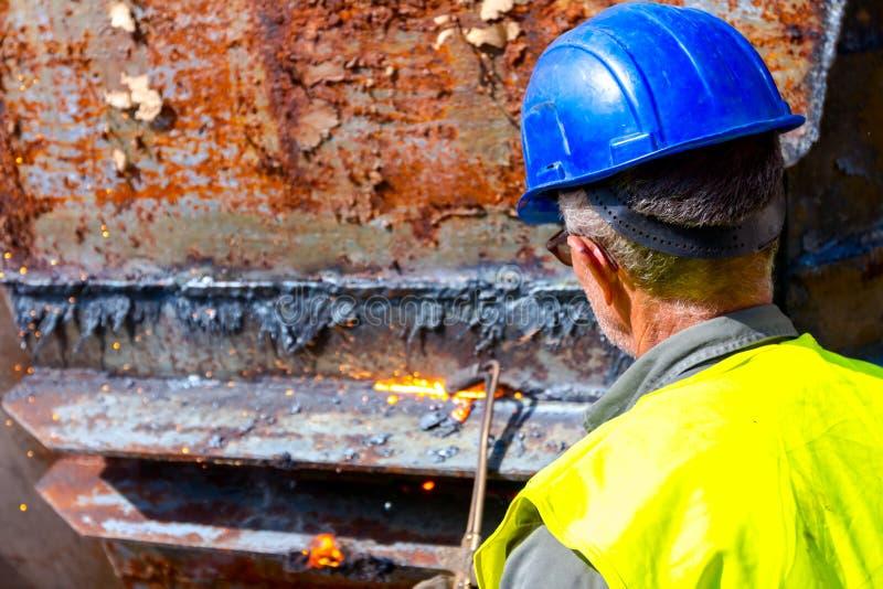 工作者切开老有乙炔火炬的金属工业设备 库存照片