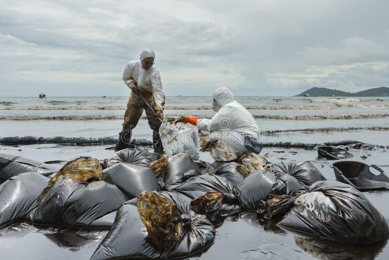 工作者去除并且清扫原油从溢出的Prao海湾 库存图片