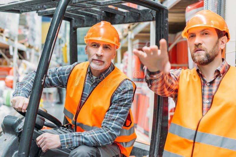 工作者和他的资深同事与铲车机器一起使用 免版税库存照片