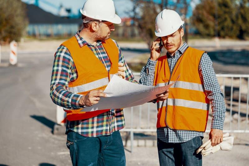 工作者和咨询关于项目的建筑经理与英语 库存照片