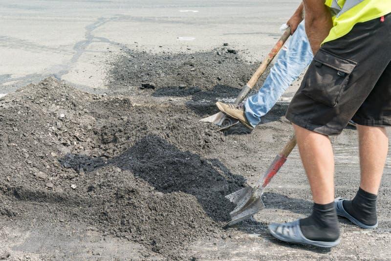 工作者和机械工作有沥青和石渣的,陆运,路修理wor的街道建筑被铺的路 免版税库存图片