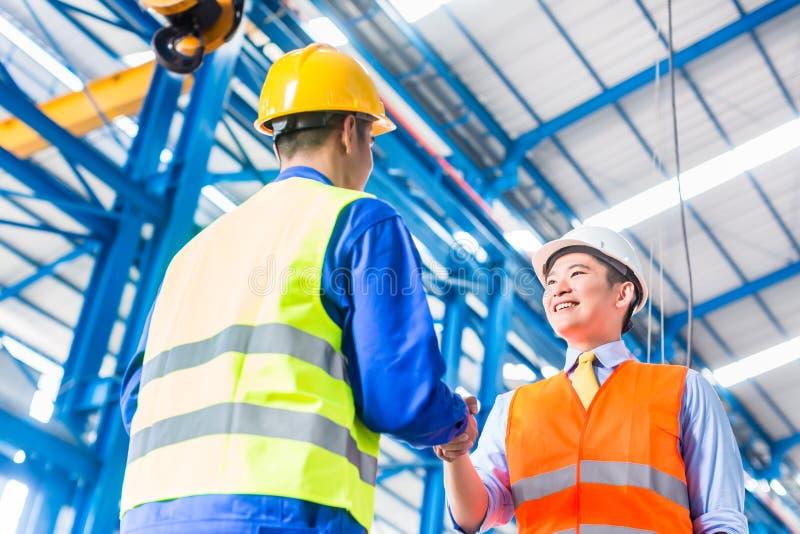 工作者和顾客有协议在工厂 图库摄影