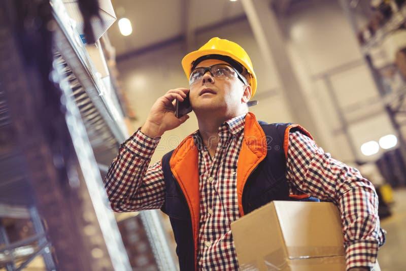工作者在仓库里物品为急件做准备 免版税图库摄影