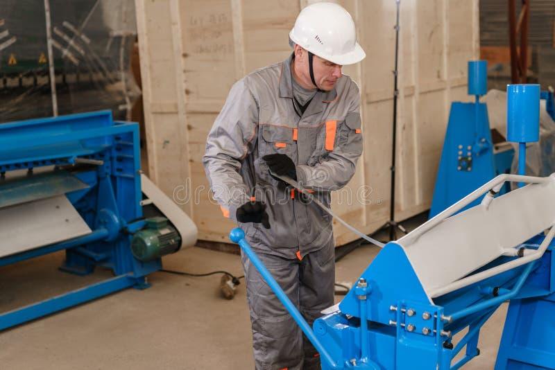 工作者在仓库里调整机器 透气和天沟的生产 工具和弯曲的设备为 免版税库存图片
