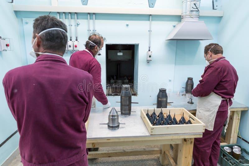 工作者在军火工厂临近弹药机器 免版税图库摄影