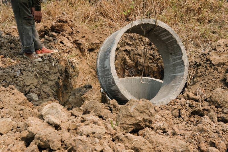 工作者在地面的埋葬管子做的在工地工作的化粪池 免版税图库摄影