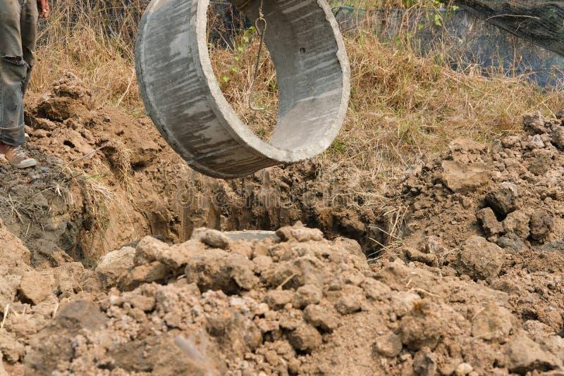 工作者在地面的埋葬管子做的在工地工作的化粪池 免版税库存照片