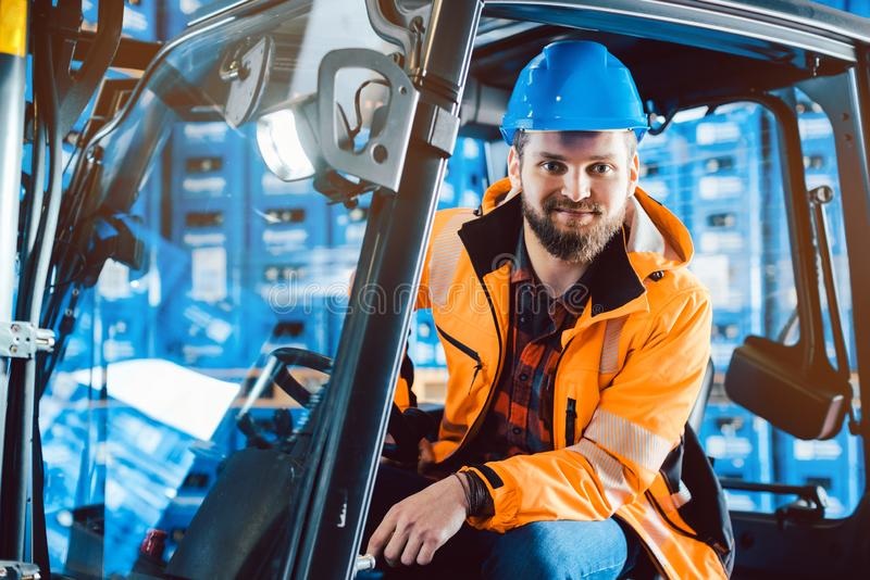 工作者在坐在他的铲车的仓库里 免版税库存照片